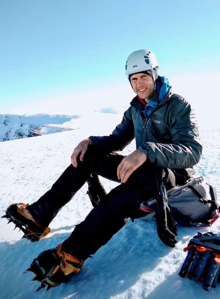 Climber sat on a snowy plateau in bright sunshine.