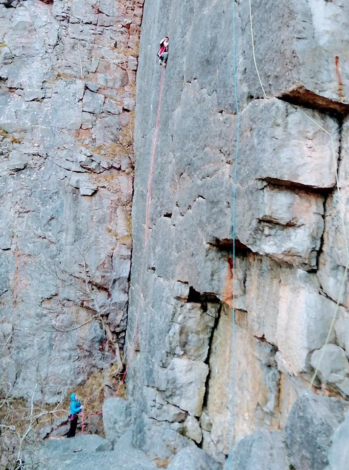 Climber high on a featureless rock wall.