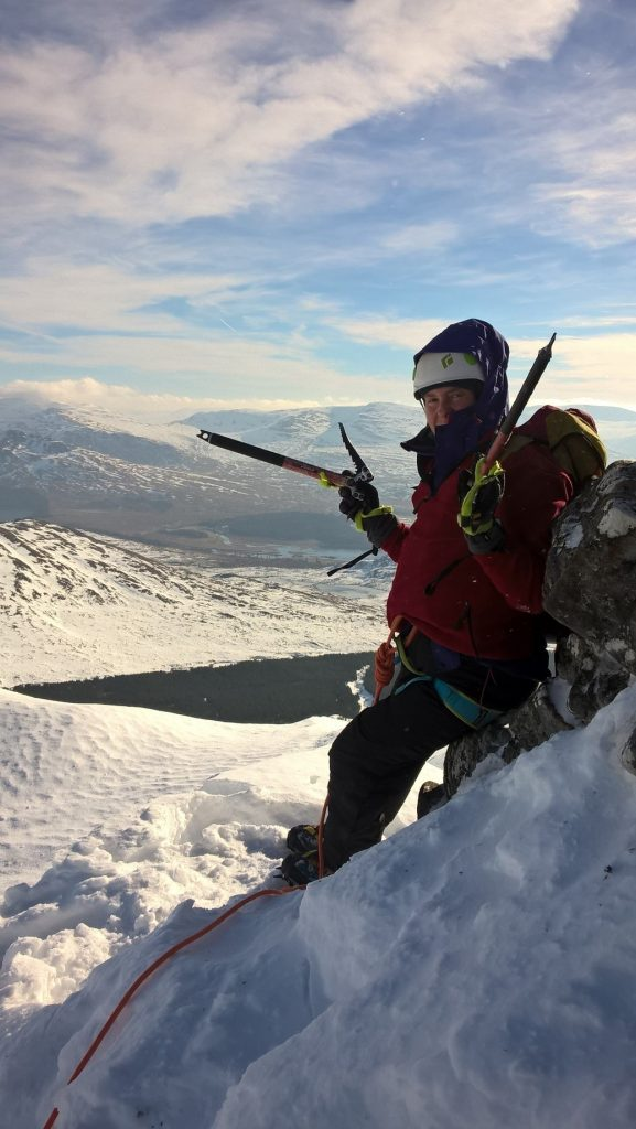 Climber on a snowy ridge, holding an ice axe.