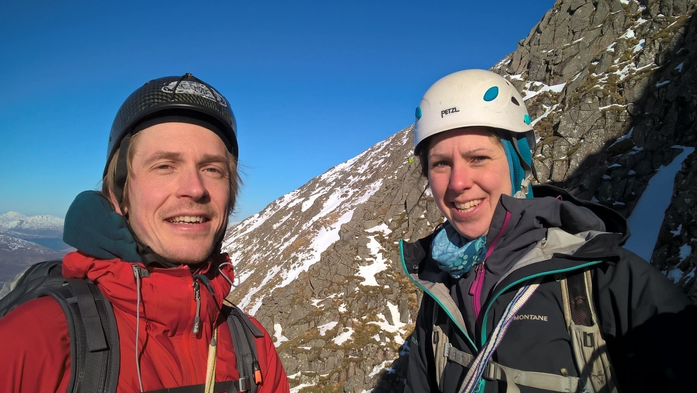 Two climbers in front of a rock slope.