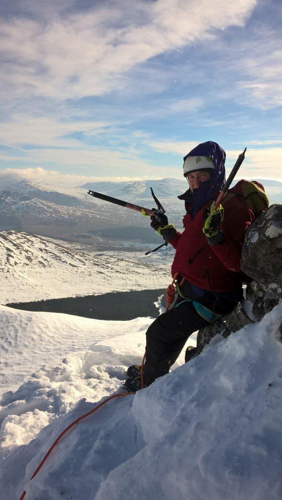 Climber on a snowy ridge, holding an ice axe.